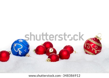 red and blue christmas balls in snow - isolated - stock photo