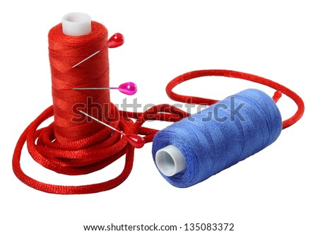 Red and blue coils of threads, band and pins  on a white background