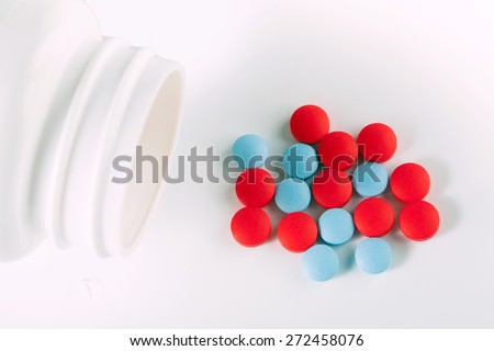 red and blue drug pills on white table - stock photo