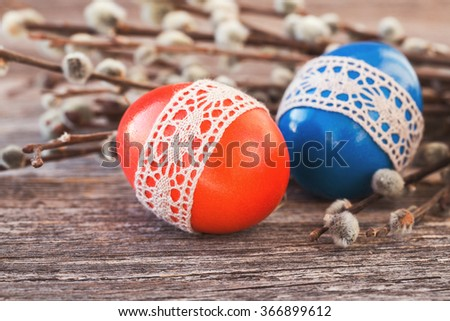 Red and blue Easter eggs decorated with lace  on wooden background. Toned, selective focus - stock photo