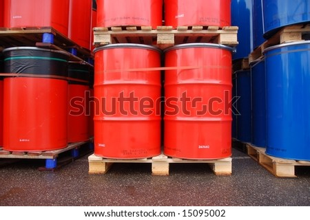Red and blue oil drums on wooden pallets