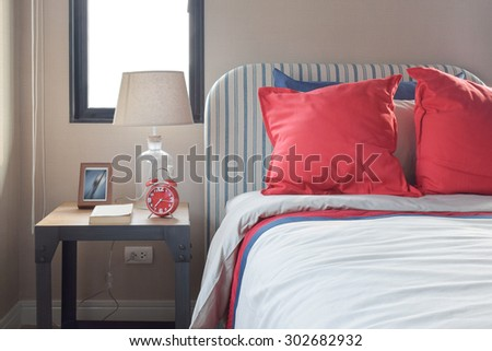 Red and blue pillows on the cozy bed with striped headboard - stock photo