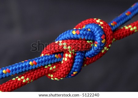 Red and blue rope tied together in a figure eight knot.