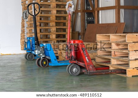 Red and blue stacker trucks with wooden pallets.