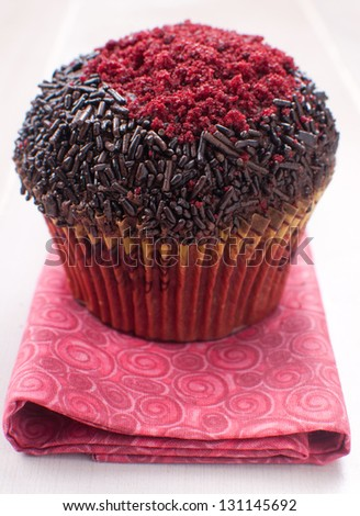 Red and chocolate decorated muffin on napkin
