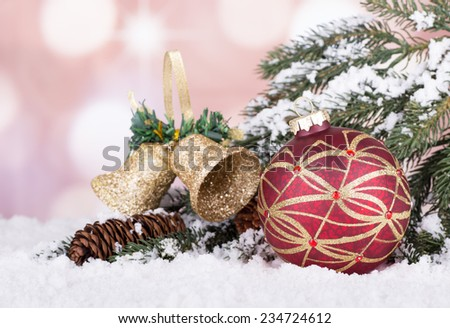 Red and gold Christmas ball with evergreen branch, bells and pine cone on snow