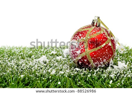 red and golden christmas ball on the grass with snow - stock photo