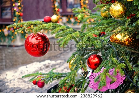 Red and golden decorating balls on the christmas tree at the street market - stock photo