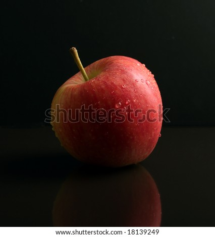Red and Green Apple on black reflective surface