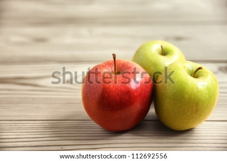 red and green apples on wooden table - stock photo