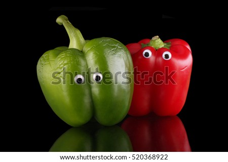 Red and green bell peppers, humourously posed as friends or partners.