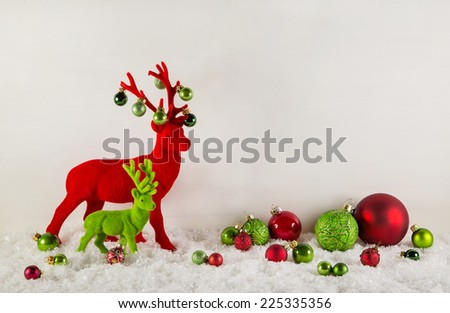 Red and green christmas decoration with snow: Reindeer with balls on wooden white background. - stock photo