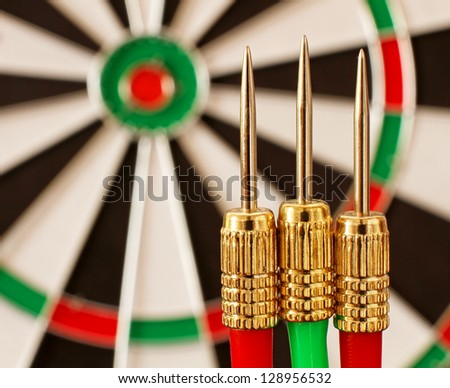 Red and Green Darts and a Dart Board in narrow focus (Original image of the world is a public domain image from NASA) - stock photo