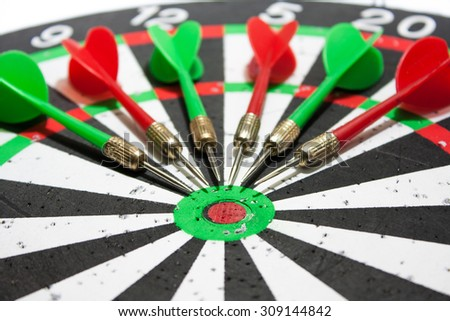 Red and green darts laying on the dart board.