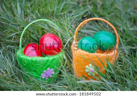 red and green eggs in baskets are hidden in the grass,best focus rim and orange flower in a basket