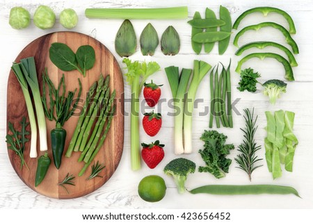Red and green fresh super food with vegetable and fruit selection over distressed white wood background. High in vitamins, antioxidants, minerals and anthocyanins. - stock photo