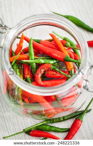 Red and green hot chili pepper in a glass jar - stock photo