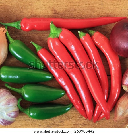 Red and green hot chili peppers on old wooden table. - stock photo