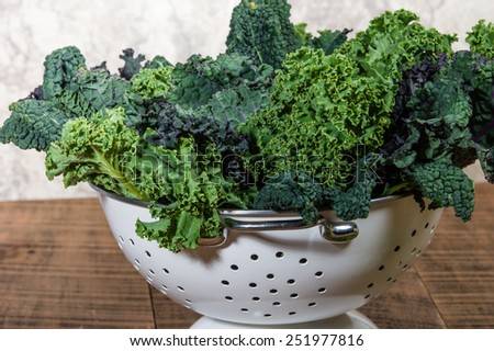 Red and green kale leaves in a white colander - stock photo