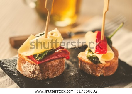 Red and green peppers with cheese, spanish tapas. Vintage edition. - stock photo