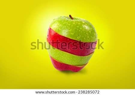 Red and green sliced apple on yellow background. - stock photo