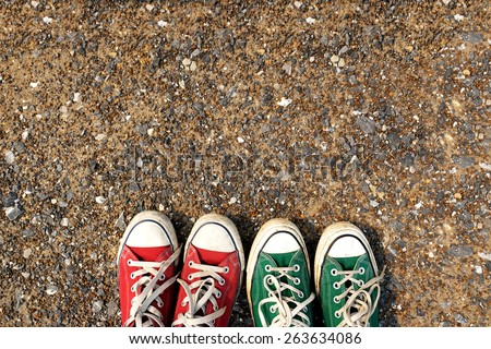 Red and green Sneakers shoes walking on gravel road , Canvas shoes walking on gravel road , two sneakers behind each others as a sign of love , Sneakers shoes Couple  - stock photo