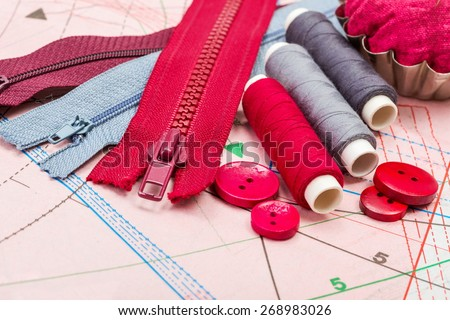 Red and grey sewing accessories on pattern cutting - stock photo