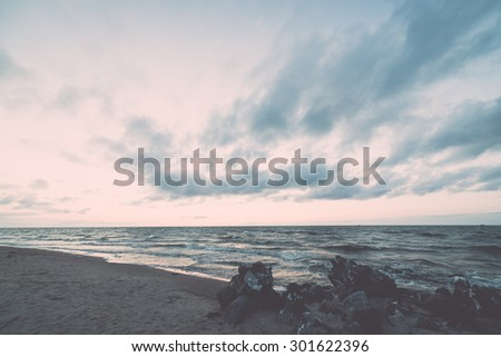 red and orange dramatic sunset on the sea beach with colorful sky- vintage retro effect - stock photo