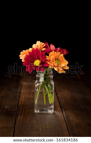 red and orange flowers in a small glass bottle on an old wooden floor with copy space