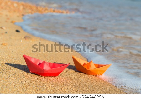 red and orange paper boats at the beach to play with