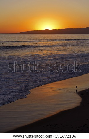 Red and Orange sky over the ocean on the Beach - stock photo