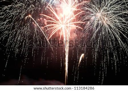 Red and purple colorful holiday fireworks on the black sky background. - stock photo