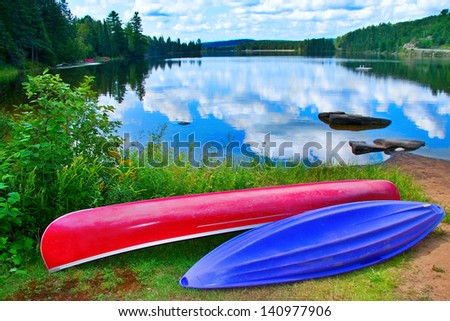 red and purple kayak on the edge of a lake in Ontario Canada - stock photo