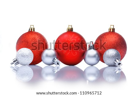 Red and silver Christmas decorations in a row with reflections and copyspace for your Christmas greetings or wishes - stock photo