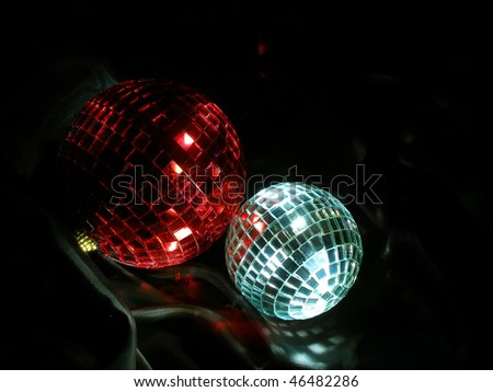 Red and silver disco balls on black silk - stock photo