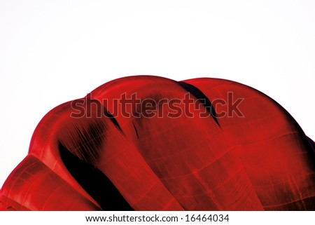 Red and white abstract image of hot air balloon inflating with plenty of copy space.