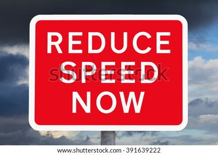 Red and white british warning roadsign REDUCE SPEED NOW  in front of a sky with very dark clouds - stock photo