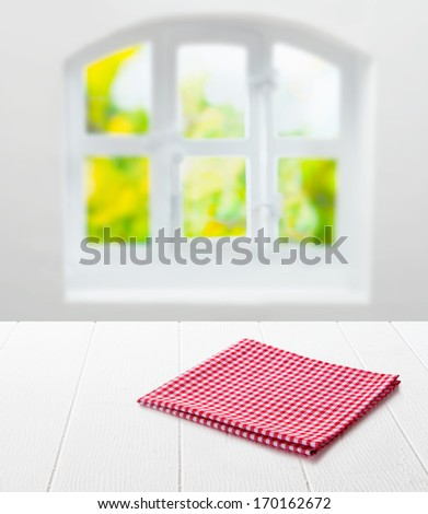 Red and white checked cloth neatly folded on top of an empty clean white table top under a window with a view of summer greenery in a country kitchen - stock photo
