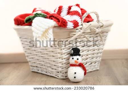Red and white Christmas clothes in a wicker basket with handmade crochet snowman, isolated on white