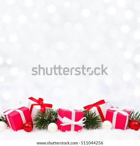 Red and white Christmas gifts in snow with branches and twinkling silver background