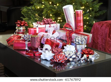 red and white christmas presents with bows on coffee table by tree - stock photo