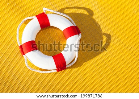 red and white colored life belt in front of a yellow background - stock photo