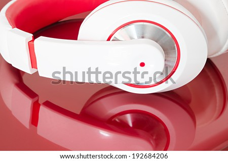 Red and white colorful headphones on bordo laptop mirrored surface - stock photo