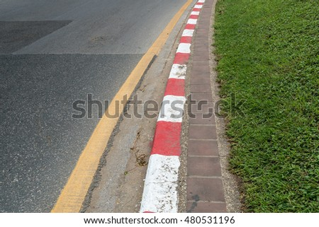 Red and white concrete sidewalk curb with green grass