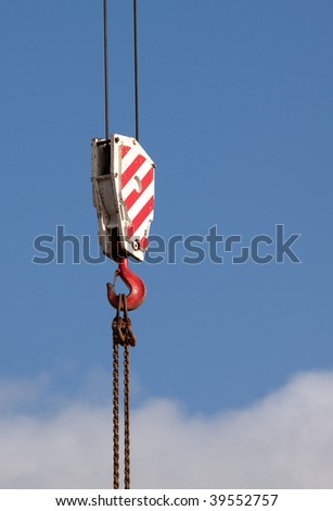 Red and white crane hook against a blue sky