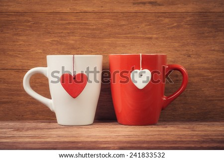 Red and white cups with heart shapes over wooden background - stock photo