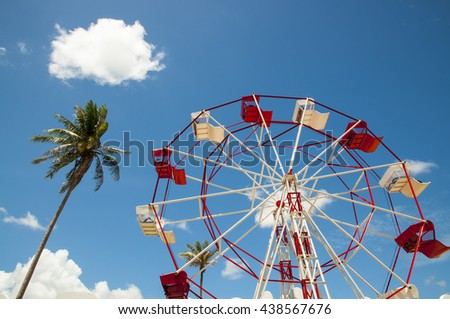 Red and white ferris wheel and coconut  tree against a sky background - stock photo