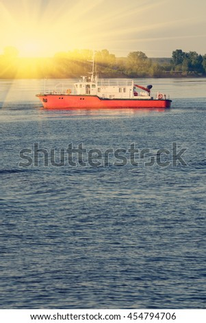 Red and white fishing trawler or boat afloat. Sunny, toned