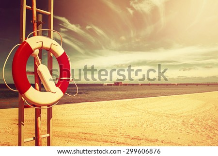 red and White Lifebuoy on Sandy Beach of Coastal Summer Vacation Resort - stock photo