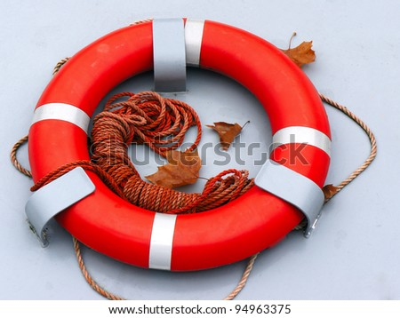 Red and white lifebuoy ring hanging on a wall - stock photo